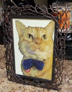 a detailed cross stitch of an orange cat in a blue bowtie